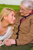 Together. A young woman  together whit an older one talking, smiling at her - part of a series Royalty Free Stock Photo