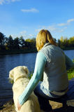 Together in beautiful nature. Woman sitting with her dog golden retriever in nature near the river in beautiful autumn day royalty free stock photo