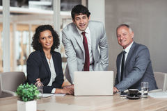 Together they can achieve business success. Portrait of three diverse businesspeople working together over a laptop at a table in an office boardroom Royalty Free Stock Photography