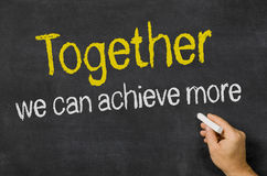 Together we can achieve more. Blackboard with the text Together we can achieve more royalty free stock image