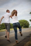 Together cheerfully to walk... The guy and the girl go on highway, having joined hands royalty free stock photo