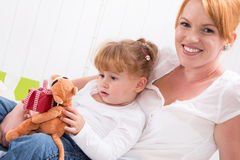 Together: daughter sitting on mother's lap with present isolated Stock Photos