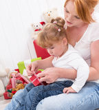 Together: daughter sitting on mother's lap with present isolated Royalty Free Stock Images
