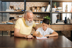 Caring grandfather helping his grandson with home assignment. Together easier. Cheerful elderly men sitting at the table next to his pre-teen grandson and Royalty Free Stock Photo