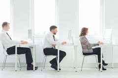 Together everyone achieves more. Two men and women sitting beside computers in light, modern office Royalty Free Stock Photo