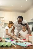 Beautiful daughters with nice hairstyles cooking together with father royalty free stock images