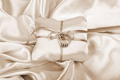 Together forever. Wedding and diamond engagement rings on silk presentation cushion royalty free stock images
