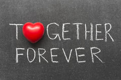 Together forever. Phrase handwritten on blackboard with heart symbol instead of O royalty free stock photos