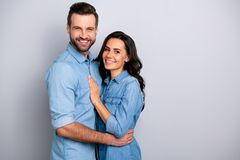 Together forever. Portrait of handsome charming married people spouses isolated feeling cheerful joyful wearing denim. Shirts on silver background royalty free stock images
