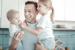 Joyful caring man smiling and playing with children. royalty free stock image