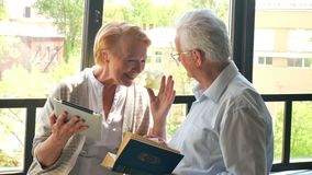 Always together. Happy lovely retired couple standing opposite each other and laughing stock footage