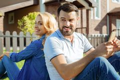 Happy couple sitting back to back in backyard Royalty Free Stock Photos