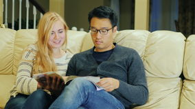 Together reading a magazine. Young multi-ethnic couple spends time at home. Together reading a magazine. Young authenticmulti-ethnic couple spends time at home stock footage