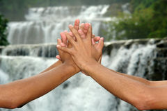 Together save the Earth. Linked hands in front of a waterfall, symbolizing a joint effort to save the environment and the planet Royalty Free Stock Photo