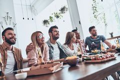 Together since school. Group of young people in casual wear communicating and smiling while having a dinner party stock images