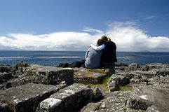 Together in Scotland. Two people sitting on the rock near the ocean Royalty Free Stock Photos