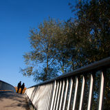 Together we stand. Silhouette of a couple standing on a bridge from lower angle Stock Photo