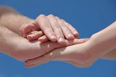 Together we stand as one. Some people putting her hands together in front of a bright blue sky Stock Images
