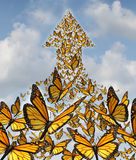 Together For Success. Business concept with monarch butterflies flying in a large union of organized group partnership forming an arrow going up to the sky as a Stock Photography
