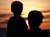 Together in sunset. Silhouettes of mother and sun looking at sunset Stock Photos