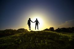 They are together to the end. The photo shows two silhouettes lovelyl people in a jump Stock Photography