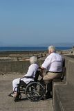 Togetherness. Elderly woman in a wheelchair sitting next to an elderly man, gazing at a sea view Royalty Free Stock Photos