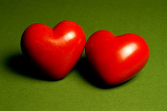 Togetherness. Two red hearts on a green background royalty free stock images
