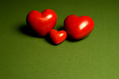 Togetherness. Two bigger and on smaller heart on a green background. With space for copy stock photography