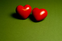 Togetherness. Two hearts on a green background. With space for copy royalty free stock photos