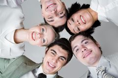 Togetherness. Below view of five friends looking at camera with their heads next to each other Stock Photo