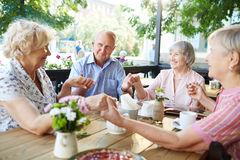 Togetherness. Group of friendly seniors holding by hands by table Royalty Free Stock Images