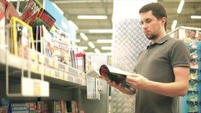TOGLIATTI, FEDERACIÓN RUSA - 7 DE JULIO DE 2017: Hombre joven que elige una revista almacen de metraje de vídeo
