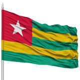 Togo Flag on Flagpole. Flying in the Wind, Isolated on White Background Royalty Free Stock Photo