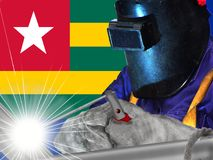 Welder and flag of Togo. Togo, a West African nation on the Gulf of Guinea, is known for its palm-lined beaches and hilltop villages. Koutammakou, inhabited by Royalty Free Stock Photo