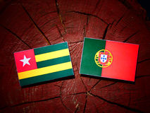 Togolese flag with Portuguese flag on a tree stump isolated. Togolese flag with Portuguese flag on a tree stump royalty free illustration