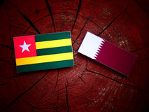 Togolese flag with Qatari flag on a tree stump isolated. Togolese flag with Qatari flag on a tree stump Royalty Free Stock Photos