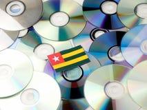 Togolese flaga na górze cd i DVD stosu odizolowywającego na bielu Fotografia Royalty Free