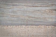 Toile à sac tissée sur la texture du bois. Photo stock