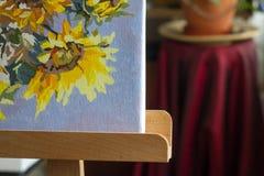 Toile, peinture, brosses, couteau de palette se trouvant sur la table Photos libres de droits