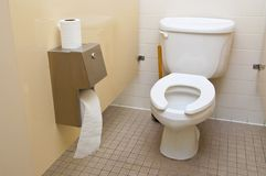 Toilet. A roll of toilet paper next to a toilet in a bathroom royalty free stock photos