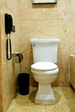 Toilet. In bathroom with linoleum floor, and a phone hanging on the wall Royalty Free Stock Image