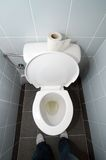 Toilet. Empty clean white toilet and toilet paper on it, man standing in front of it Royalty Free Stock Images
