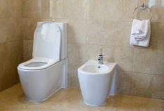 Toilet and bidet. In a marble tiled bathroom Stock Photography