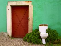 Toilet bowl. Near old rusty iron door Stock Photography