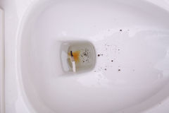 Toilet bowl with extinguished cigarette. Butt royalty free stock photo