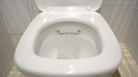 Toilet Bowl is washed off by the water. Luxury bright toilet bowl is washed off by the clear water stock video