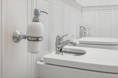 Toilet and detail of a corner shower bidet with soap and shampoo dispensers on wall mount shower attachment stock image