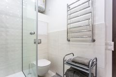 Toilet and detail of a corner shower cabin with wall mount shower attachment royalty free stock image