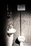 Toilet dichtbij wasbak onder de spiegel met scheerbeurtborstel op s Stock Fotografie