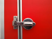 Toilet door latch On the bright red ground.  Royalty Free Stock Photos